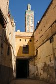 A typical small alley and a minaret of a mosque in the city of Fes on a beautiful day wiht blue sky and no clouds in Morocco. poster
