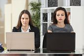Front view of two angry businesswomen looking each other with hate working with laptops at office poster