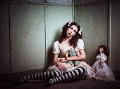 Strange sad girl with dolls sitting in the forsaken place poster
