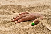 on the beach hand in rigor mortis protruding from the sand poster