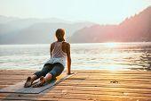 Beautiful woman practicing Yoga by the lake - Sun salutation series - Upward facing dog - Toned image poster