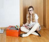 Young school girl with eyeglasses doing homework on the floor poster