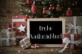 Nostalgic Christmas Card For Seasons Greetings. Christmas Tree With Balls And Snowflakes. Gifts In The Front Of Wooden Background. Chalkboard With German Text Frohe Weihnachten Means Merry Christmas poster