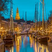 Historic sailing ships moored at quay on the annual Winterwelvaart festival around christmas. Reliving the old times in the historic part of Groningen city. poster