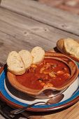 Seafood cioppino with French bread and shrimp, fish, clams, lobster, crab and scallops in tomato sauce in a pottery bowl on a dish and a cutting board. poster