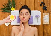 Portrait of woman patient in ayurveda spa wellness center lying on wood with aroma spa accessories. Young beautiful indian girl with ideal clean skin relax with closed eyes in beauty parlor. poster