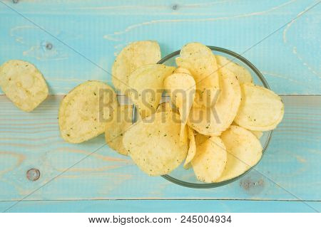 Crispy Potato Chips In Bowl On Blue Wooden Background, Top View
