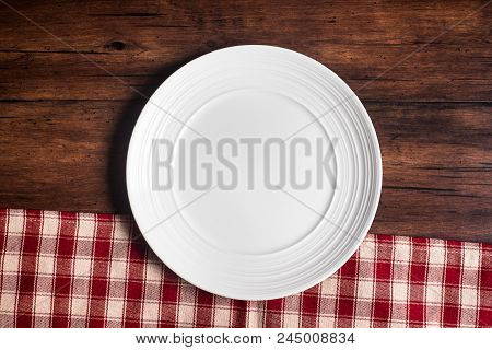 Empty White Plate On A Checkered Red Napkin On An Old Wooden Brown Background, Top View. Image With