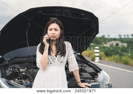 Stressed Asian Woman With A Broken Car Using Mobile Phone To Call Assistance On Roadside. Accident A