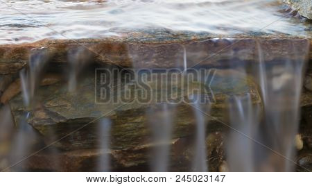 Water Rolling Over A Small Cascade Of Brown And Gray Rocks