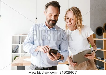 Couple of smiling colleagues looking at mobile phone together while standing at the office