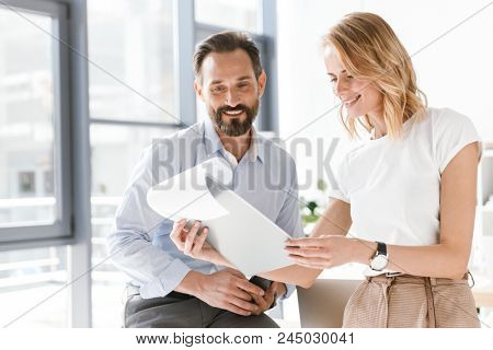 Confident man manager using mobile phone while leaning on a desk at the office with woman co worker showing him paperwork paperwork