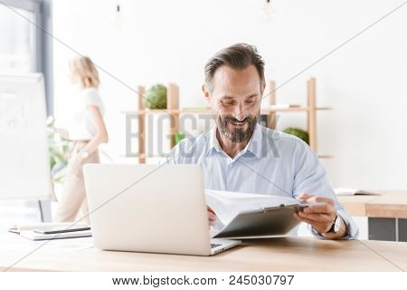 Friendly man manager working on laptop computer with documents while sitting at the office with woman co worker on a background