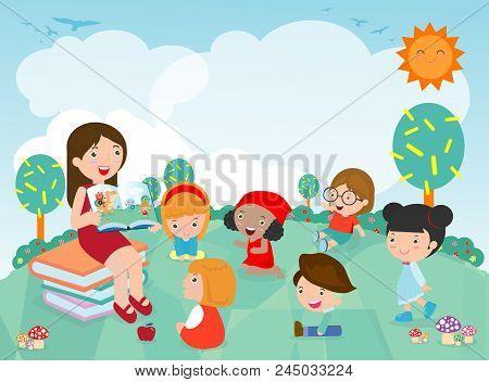 Teacher Telling A Story To Nursery Children In The Garden, Cute Kids Listening To Their Teacher Tell