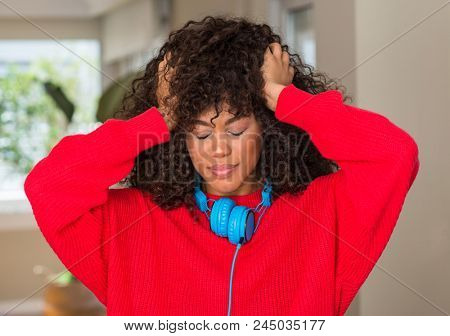 African american woman wearing headphones suffering from headache desperate and stressed because pain and migraine. Hands on head.
