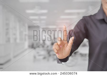 The Woman Touches The Imaginary Screen With Her Finger. Background Blur Emergency Room