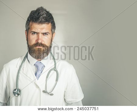 Serious Doctor With Stethoscope In Clinic In Surgical Uniform. Physician With Serious Face Ready To