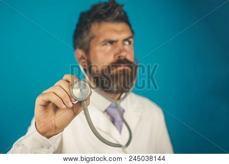 Doctor, Male Physician With Stethoscope In Hand, Focus On Stethoscope. Doctor Holds In Hand Stethosc