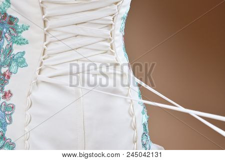 The Bride Is Helped To Lace Up The Corset