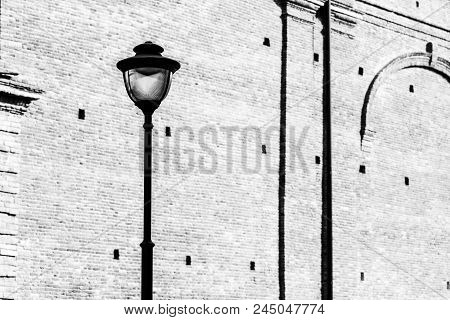 One Elegant Street Electric Lamppost On An Indistinct Background Of An Old Brick Wall Of Monochrome