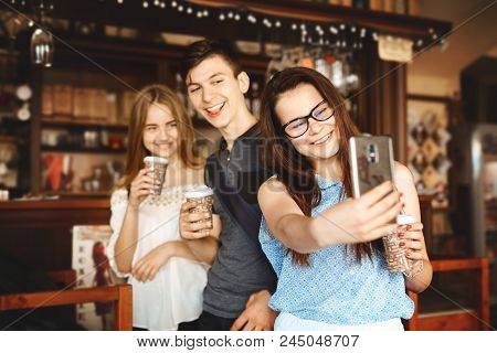Group Of Friends Enjoying In Cafe Together. Young People Meeting In A Cafe. Young Men And Women With