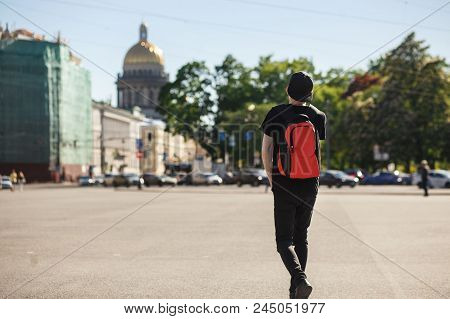 Back view of young stylish man tourist walking at Palace square near Saint Isaac's Cathedral in Saint-Petersburg. He wearing in black jeans, black T-shirt, black cap and red backpack. poster