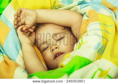 Small Baby Dreaming. Sleepy Baby In Colorful Blanket. Child Sleep In Bed. Trust And Tenderness. Chil
