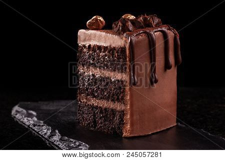 Piece of chocolate cake. Chocolate mousse cake slice on a black board, black background. Chocolate Treat. poster
