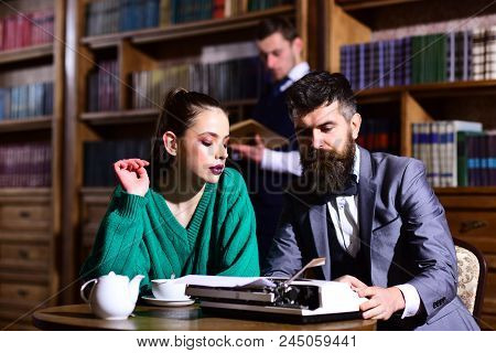 Agile Business And Grammar Concept. Couple In Library With Typewriter And Teapot Drinking Coffee Fro