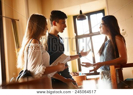 Group Of Friends Enjoying In Cafe Together. Young People Meeting In A Cafe. Young Man And Women Sitt