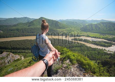 Follow me concept - Woman wanting her boyfriend to follow her in travel on the top of mountain in Altai