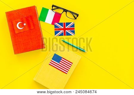 Language Study Concept. Textbooks Or Dictionaries Of Foreign Language Near Flags On Yellow Backgrond