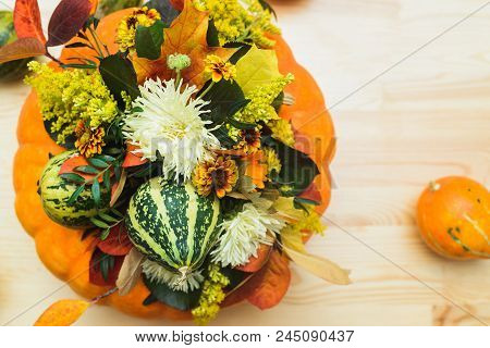 Autumn Bouquet Of Decorative Pumpkins, Flowers And Leaves In A Vase Of Orange Pumpkin On A Wooden Ta