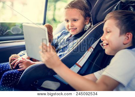 Sister and brother playing with digital devices in the car