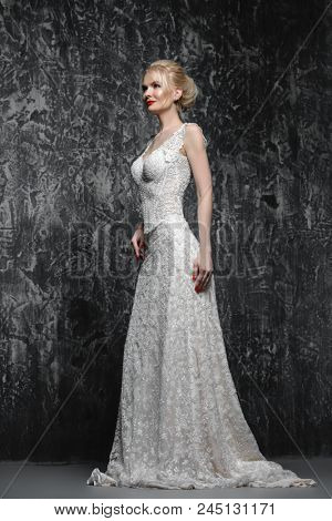 Beautiful bride woman wearing lace white wedding dress posing over grunge background. Full length portrait. Beauty, wedding fashion.