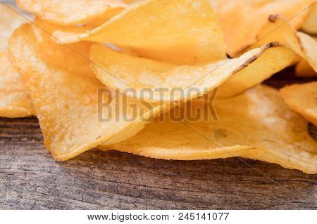 Close-up View Of Heap Of Potato Chips On Wooden Background