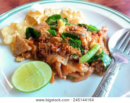 Stir Fried Flat Noodle With Chinese Kale, Soy Sauce And Pork In White Dish. Thai Style Food.