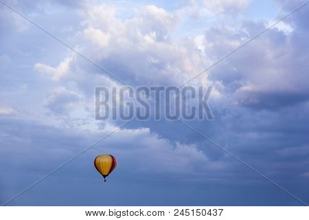 A Balloon With A Basket Filled With Hot Air, Flies In The Blue Sky. An Air Balloon In The Blue Sky.