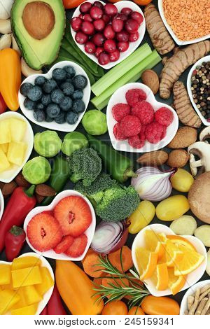 Healthy super food concept with fruit, vegetables, herbs spice and nuts in heart shaped dishes and loose. Foods high in antioxidants, omega 3 fatty acids, fibre,vitamins, minerals and anthocyanins.