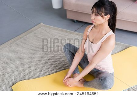 High Angle View Of Beautiful Young Woman Practicing Yoga In Bound Angle Pose At Home