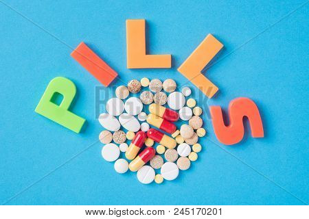 Different Tablets And Pill Painkillers In The Package And Without It On A Blue Background