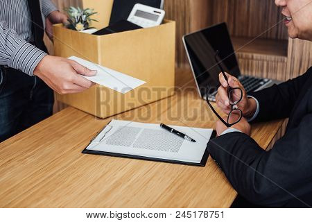 Image of businessman hand holding cardboard box and sending a resignation letter to his boss, change of job, unemployment, resign concept. poster