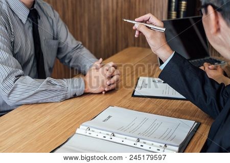 Two Senior Manager Reading A Resume During A Job Interview, Employer Interviewing To Ask Young Male