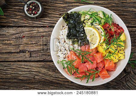 Hawaiian salmon fish poke bowl with rice, avocado, mango, tomato, sesame seeds and seaweeds. Buddha bowl. Diet food. Top view. Flat lay poster