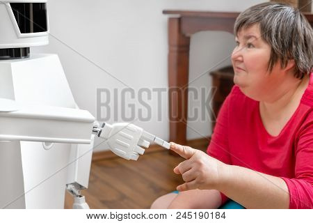 Autonomous Medical Service Robot Is Touching With His Finger The Finger Of An Mentally Disabled Woma