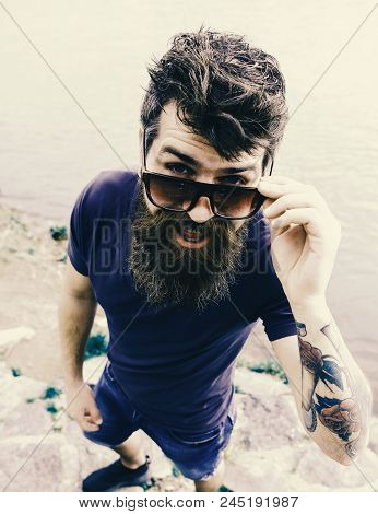Man And Mustache Wears Sunglasses, Water Surface On Background. Hipster On Cheerful Face With Fashio