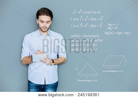 Geometry Lesson. Attentive Diligent Student Looking Concentrated While Holding A Pencil And Making N