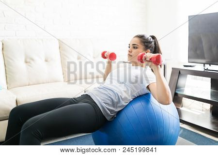 Latin Woman Exercising With Dumbbell Using A Stability Ball For Support In Living Room