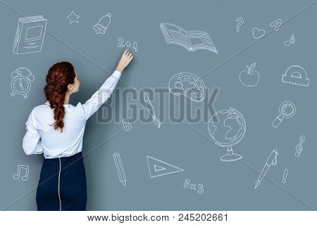 Writing On The Blackboard. Attentive Clever Teacher Standing In Front Of The Blackboard And Holding
