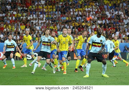 Nice, France - June 22, 2016: Swedish (in Yellow) And Belgian Players Fight With Each Other For A Ba